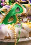 Mardi Gras: Den gröna maskeringen sitter i mitt av den traditionella konungen Cake Royaltyfria Foton