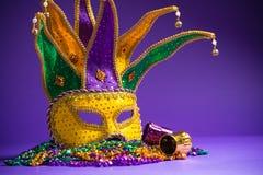 Mardi Gras eller Carnivale maskering på en purpurfärgad bakgrund arkivbild