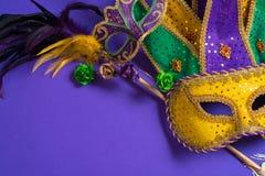 Mardi Gras eller karnevalmaskering på purpurfärgad bakgrund Arkivbilder