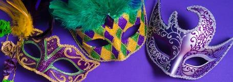 Mardi Gras eller karnevalmaskering på purpurfärgad bakgrund Arkivbild