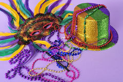 Mardi Gras feathered masks party hat beads. Mardi Gras still life feathered masks shiny party hat beads with copy space for text - part of series-also Stock Image