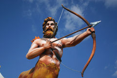 Mardi Gras Float Archer. Mardi Gras float character with bow and arrow against a blue sky and clouds Stock Photo