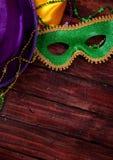 Mardi Gras: Grön maskerings- och lilahatt med halsband Royaltyfri Bild