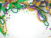 Mardi Gras. Green, gold and purple colors in beads, ribbon and confetti with a harlequin mask stock photos