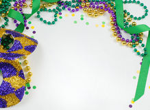 Mardi Gras. Green, gold and purple colors in beads, ribbon and confetti with a harlequin mask stock images