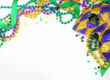 Mardi Gras. Green, gold and purple colors in beads, ribbon and confetti with a harlequin mask
