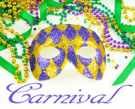Mardi Gras. Green, gold and purple colors in beads, ribbon and confetti with a harlequin mask royalty free stock photography
