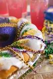 Mardi Gras: King Cake With Hurricane Drinks Behind Royalty Free Stock Image