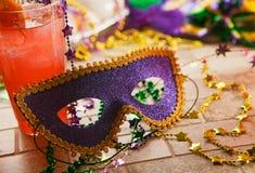 Mardi Gras: La maschera del partito si siede contro il cocktail tropicale di uragano Immagine Stock