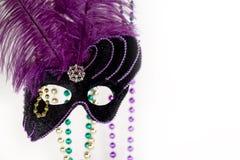 Mardi Gras Mask. Elegant purple Mardi Gras Mask with colorful beads softly blurred on white background Royalty Free Stock Photos