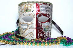 Mardi Gras mask. From New Orleans with black ribbon straps and open eye-holes, musical notes and staff decorations, and gold trim. Mardi gras beads and stock photo