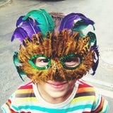 Mardi Gras mask. Smiling kid wearing Mardi Gras feathers mask Royalty Free Stock Image