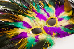 Mardi Gras Mask. Colorful mardis gras mask closeup in green gold and purple slightly out of focus on edges Stock Photos