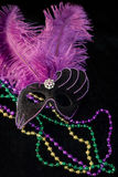 Mardi Gras Mask and Beads. Purple and black feathered Mardi Gras mask with mardi gras beads royalty free stock photography