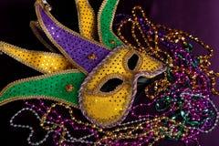 Mardi gras mask and beads on a purple background. Glittery gold, green and purple mardi gras mask with beads on a purple background