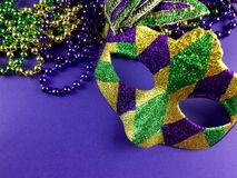 Mardi Gras. Mask and beads on a purple background
