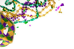 A Mardi gras mask and beads on a white background with copy space