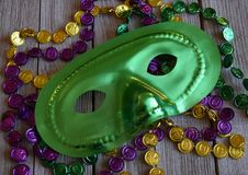 Mardi Gras mask with beads on a wood background. Green carnival mask with a string of colorful beads stock photography