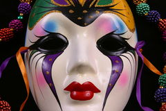 Mardi Gras Mask Closeup. Mardi Gras mask and colorful beads on a black background. Part of a series Royalty Free Stock Image