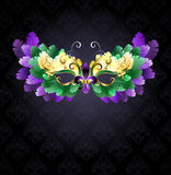 Mardi Gras mask of feathers. Mardi Gras mask of green, purple and yellow feathers on a black background stock illustration
