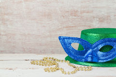 Mardi gras mask and hat for party. On wooden background