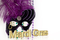 Mardi Gras Mask with text. Elegant purple Mardi Gras Mask with colorful beads softly blurred on white background, and gold 3D Mardi Gras text Royalty Free Stock Photo