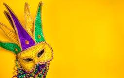Mardi Gras Mask on yellow Background. A venetian, mardi gras mask or disguise on a yellow background Royalty Free Stock Photos