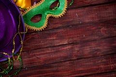 Mardi Gras: Maske und purpurroter Hut mit hölzernem Hintergrund stockbild