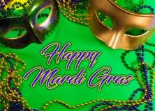 Mardi Gras maskering med pärlor på en grön bakgrund med hälsning arkivbild