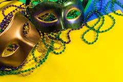 Mardi Gras maskering med pärlor på en gul bakgrund arkivfoton