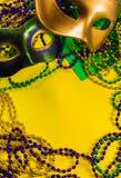 Mardi Gras maskering med pärlor på en gul bakgrund royaltyfria bilder