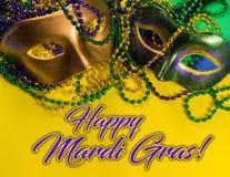 Mardi Gras maskering med pärlor på en gul bakgrund med hälsning arkivfoton
