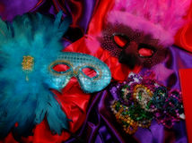 Mardi Gras Masks. And beads, on bold red and purple satin Royalty Free Stock Photo