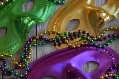 Mardi Gras masks with beads on a wood background. Gold,green, and purple carnival masks with a string of colorful beads stock images