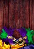 Mardi Gras: Mit Federn versehene Maske mit hölzernem Copyspace oben stockbild
