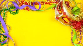 Mardi Gras overhead background with colorful masks and beads. On rustic yellow wood background, with copy space