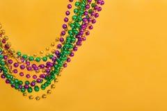 Mardi Gras pärlor mot gul bakgrund royaltyfri fotografi