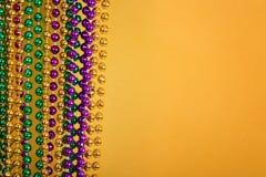 Mardi Gras pärlor mot guld- gul bakgrund arkivbild