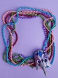 Mardi Gras pärlor och maskering som gör en ram med kopieringsutrymme på purpurfärgad bakgrund Lekmanna- lägenhet Top beskådar arkivbilder
