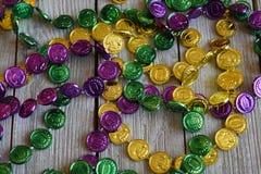 Mardi Gras pärlor på en wood bakgrund arkivbilder