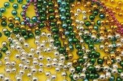 Mardi Gras pärlor på gul bakgrund arkivbilder