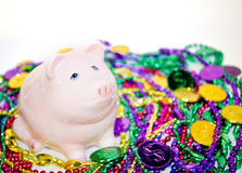 Mardi Gras Pig. Gy pank on a pile of Mardi Gras beads and coins Royalty Free Stock Photos