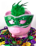 Mardi Gras Piggy Bank. Pink piggy bank in Mardi Gras mask with Mardi Gras colorful beads and coins Stock Images