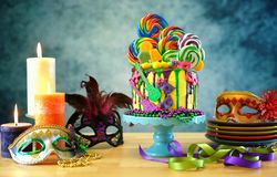 Mardi Gras theme on-trend candyland fantasy drip cake. Mardi Gras theme on-trend candyland fantasy drip cake on colorful party table setting stock photos