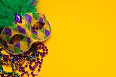 Mardi Gras or venetian mask on yellow. A festive, colorful group of mardi gras or carnivale mask on a yellow background.  Venetian masks Stock Images