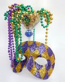 Mardis Gras. Harlequin mask and mardis gras beads spilling out of martini glass royalty free stock photos