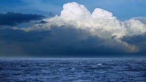 Mare agitato blu scuro, onde con schiuma bianca, nuvole torreggianti sull'orizzonte stock footage