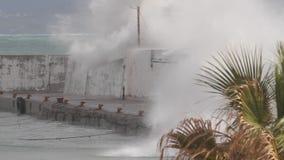 Mare agitato, onde che si rompono sopra una parete del porto durante la tempesta nel Mediterraneo archivi video