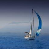Mare blu con la navigazione della barca a vela in una costa nebbiosa Immagini Stock