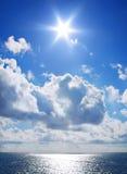 Mare blu con le nubi ed il sole Fotografia Stock Libera da Diritti